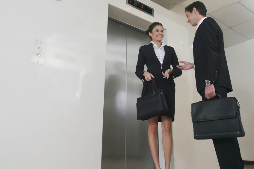 Businessman and businesswoman chatting while waiting for elevator.
